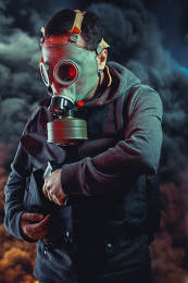 Police man with gas mask over explosion background