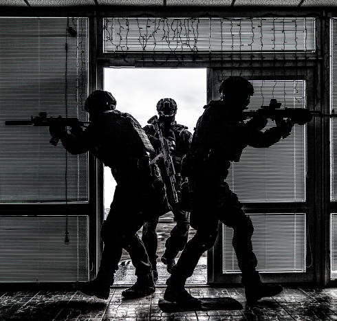 Police special anti-narcotics or counter-terrorism forces tactical team breaching door and entering in building during search and arrest warrant or hostage rescue operation, desaturated, high contrast