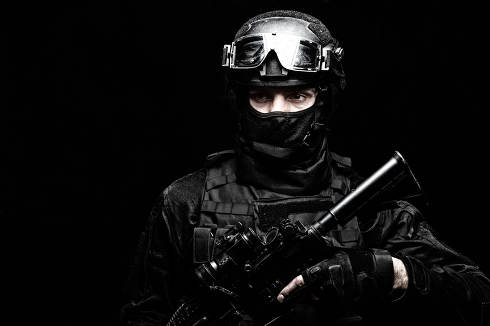 Police special operations fighter, SWAT shooter, secret service guard in black uniform, hidden behind mask identity, battle helmet with ballistic goggles, armed assault rifle, low key studio portrait