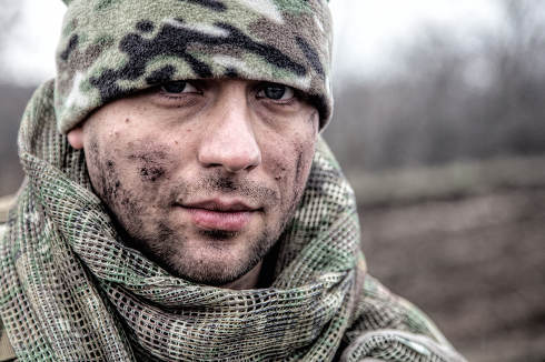 Portrait of soldier, modern combatant with dirty face, firearm replica, wearing camouflage uniform, beanie and masking cape on neck, standing on field, carrying backpack on march