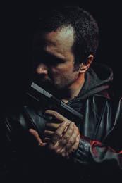 Robber with gun. Man in suit draws vintage handgun