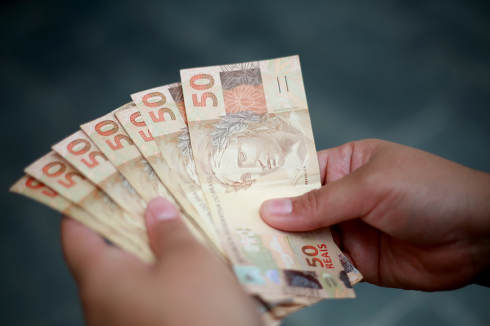 salvador, bahia Brazil, february 25, 2015, Hands hold fifty reais banknotes during counting. R$ 50