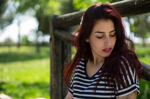 Sensual, sexy girl with long red hair in a park in summer
