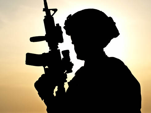Silhouette of young soldier against the sun