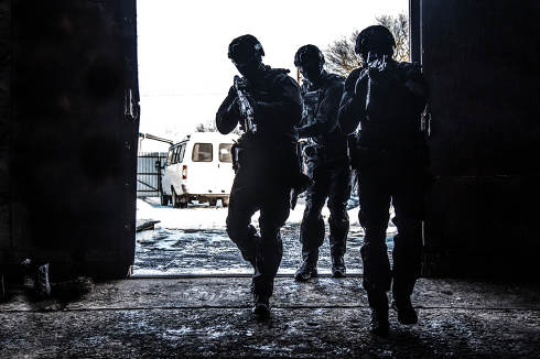 Silhouettes of police special operations forces tactical team, SWAT fighters aiming assault rifles while standing shoulder to shoulder in bright white doorway. Military tactical group storming room