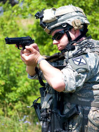 Soldier in camouflage uniform aiming his gun