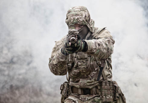 Soldier in camouflage uniform, wearing military ammunition, aiming service rifles, covering each other, shooting in competitors, attacking enemies trough smoke screen