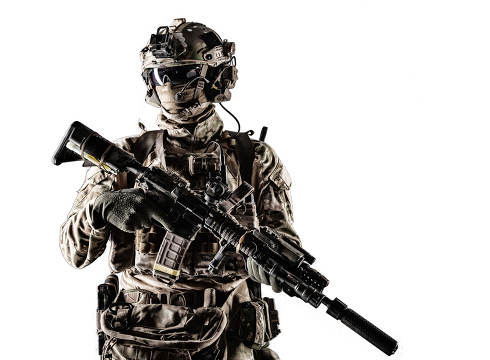 Special forces fighter in battle uniform and helmet with radio headset, face mask and ballistic glasses, standing with equipped laser sight and silencer service rifle studio portrait isolated on white