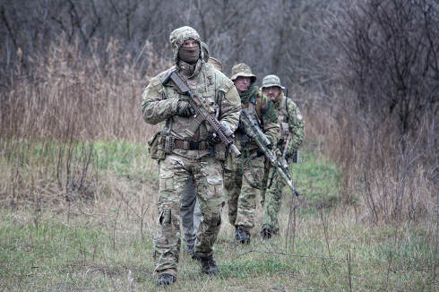 Special operations forces soldiers, elite troops tactical group, infantry fighters in combat uniforms, armed service and sniper rifles, marching in line behind commander, leader in forest or bush