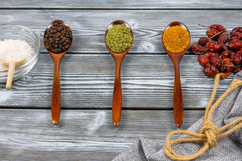 Spoons of various spices on a rustic wooden table. Top view. The concept of cooking delicious dishes