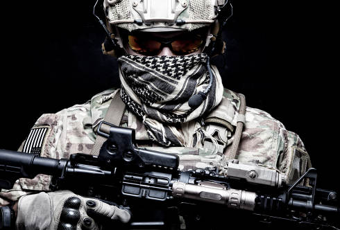 US Marine Corps soldier, army special forces fighter, modern combatant in camouflage uniform, battle helmet, tactical radio headset, face hidden behind shemagh, looking in camera, portrait on black