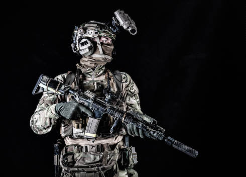 US marine riders shooter, army special forces soldier standing in darkness in mask, battle uniform, quad-tube, four lenses night vision goggles on helmet, low key, side view, studio portrait on black