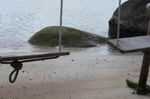 wooden swing at a sandy beach near the ocean in Koh Tao Thailand before a rainy day