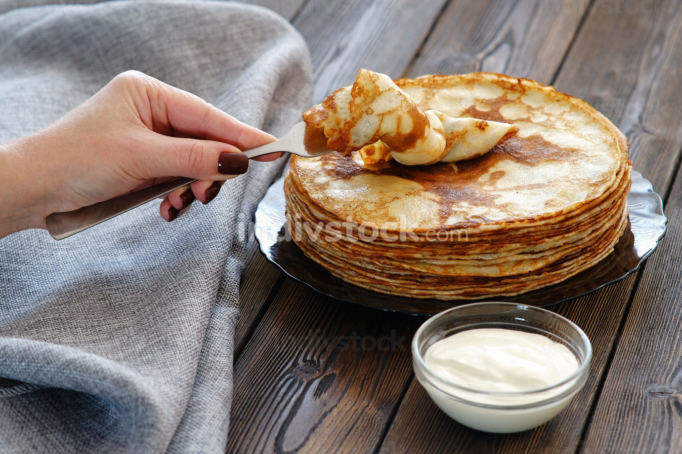 A young woman picks up a pancake with a fork. Sour cream for pancakes on the table, breakfast for the whole family. Maslenitsa, the holiday of the end of winter