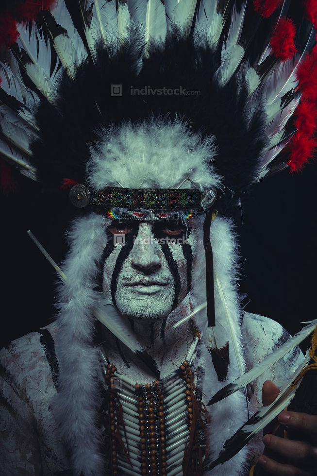 American Indian chief with feather headdress and traditional war