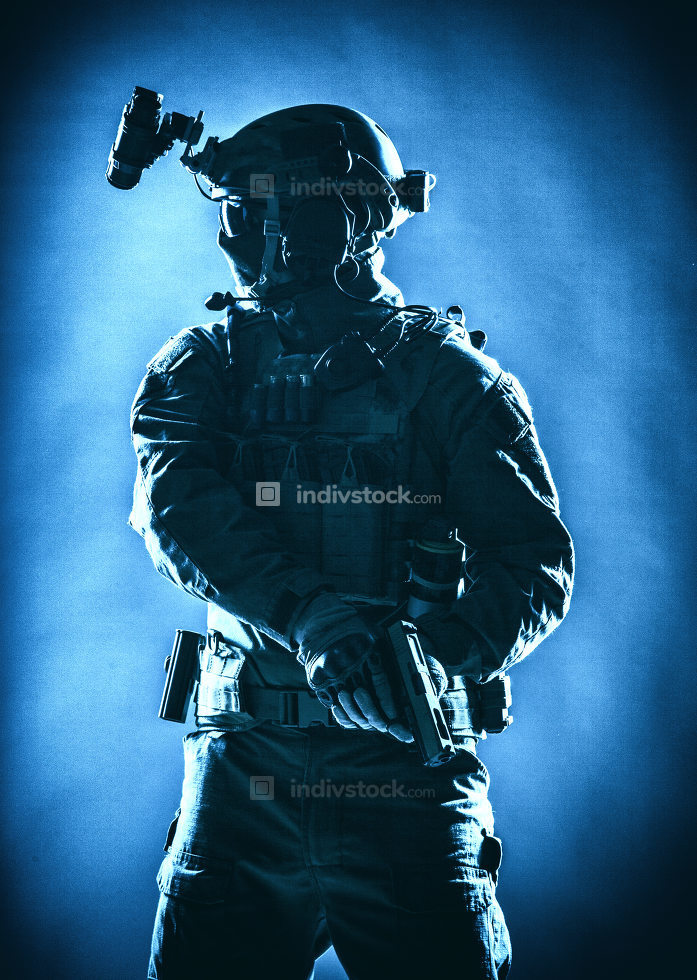 Anti terrorist squad fighter, army elite forces soldier in mask, with night vision device and tactical radio headset on helmet, armed service pistol standing ready for action, low key studio shoot