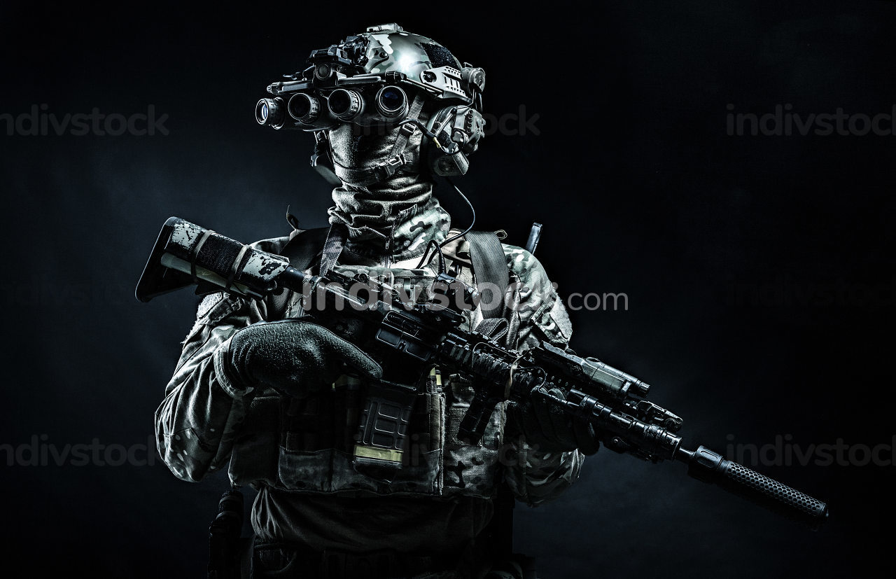 Army infantry in battle uniform, armed assault rifle with laser sight and silencer, standing in darkness, looking through night vision goggles, low key half length, studio portrait on black background