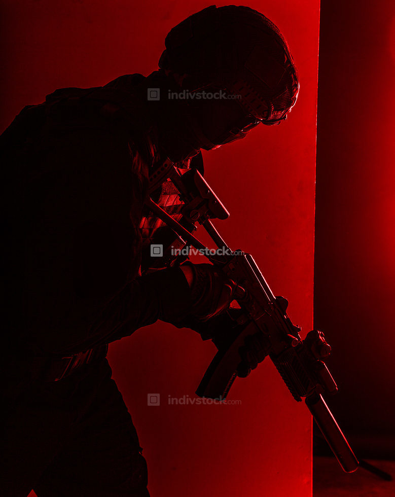 Army infantry, special operations forces soldier, police tactical team fighter with suppressed service rifle in hands sneaking trough room with red alarm light, low key studio shoot with red backlight