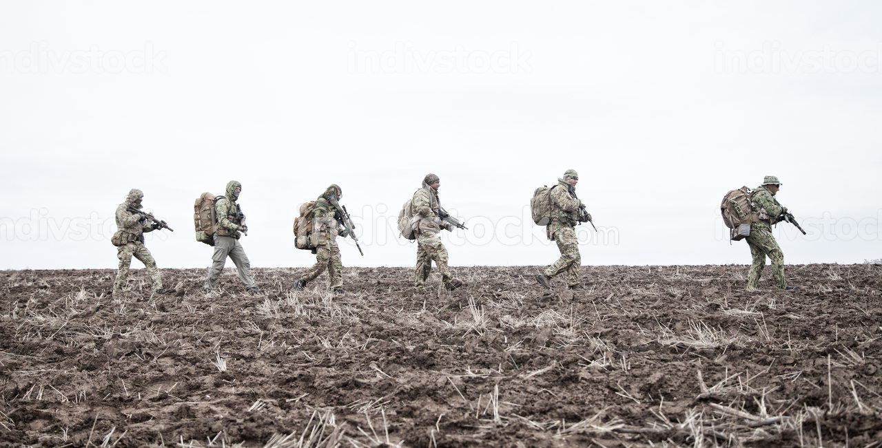 Army soldiers on march. Elite forces fighters group, commando tactical unit, reconnaissance team members in camouflage uniform, walking in line, carrying backpacks on muddy terrain