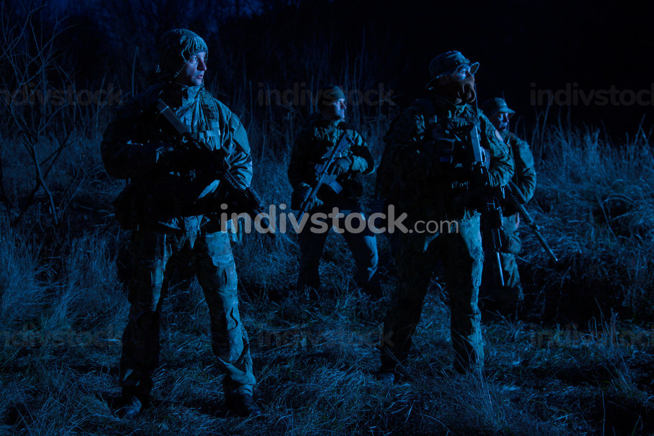 Army special operations tactical group, military saboteurs team armed fighters standing in grassy area at nighttime, hiding faces behind masks, moving silently in darkness, patrolling area at nigh