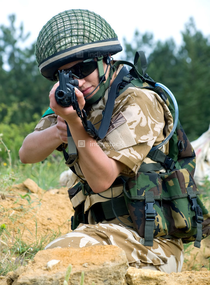 British girl soldier in desert uniform aiming her rifle