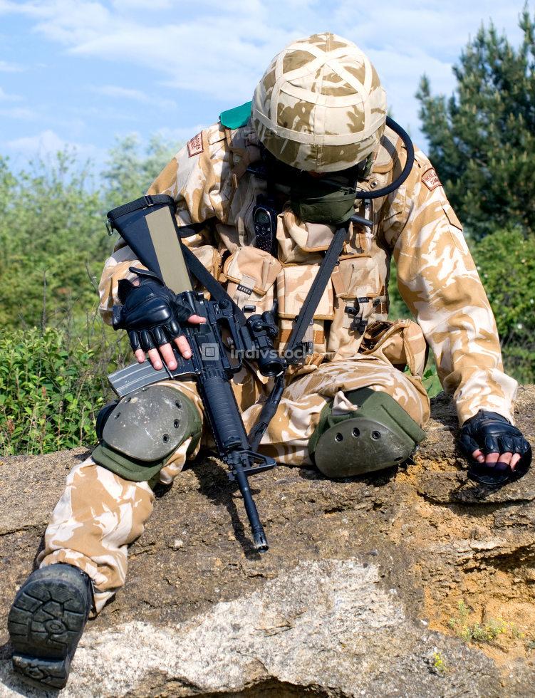 British soldier in desert uniform sitting wounded