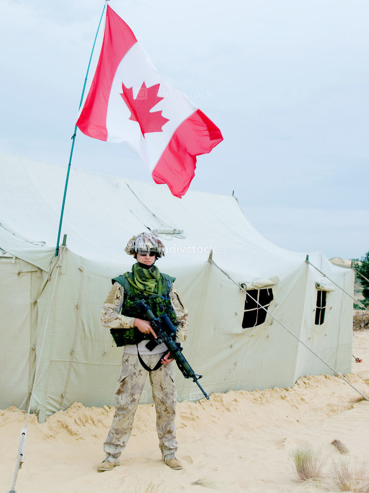 canadian soldier in desert uniform near the army tent