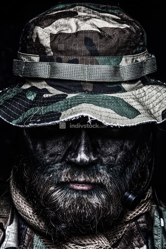 Close up, low key portrait of bearded commando fighter, army special forces soldier, private military company mercenary in boonie hat, tactical radio headset, black and green face camouflage paint