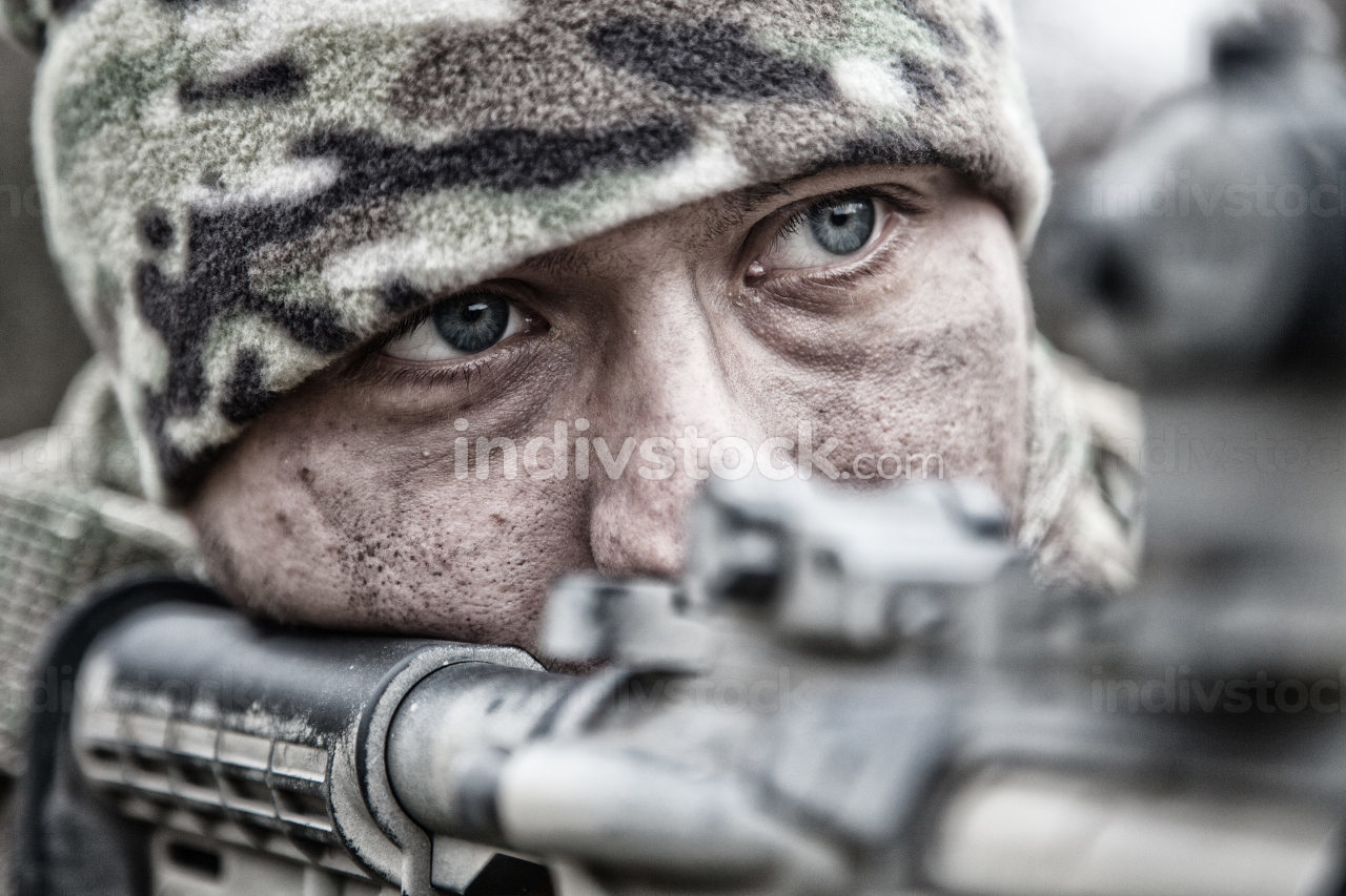 Close-up portrait of army infantryman, modern warfare combatant, young soldier with dirty, unshaven face, in camo bennie hat, aiming service rifle, controlling area with gunfire, looking in camera