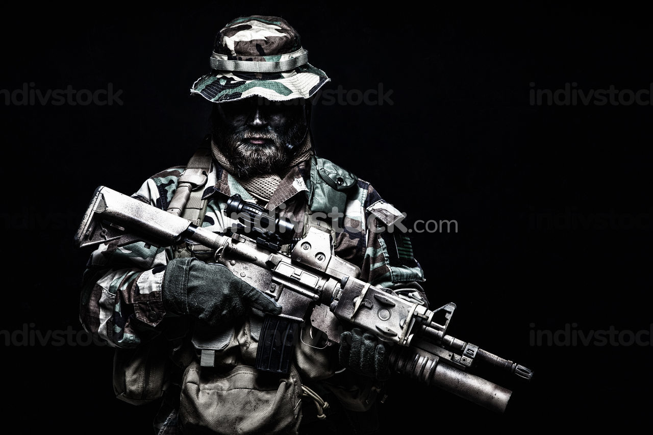 Commando shooter, army special forces rifleman in battle uniform, boonie hat, ammunition in load carrier, camouflaged with paint face, armed assault rifle, half length portrait on black background