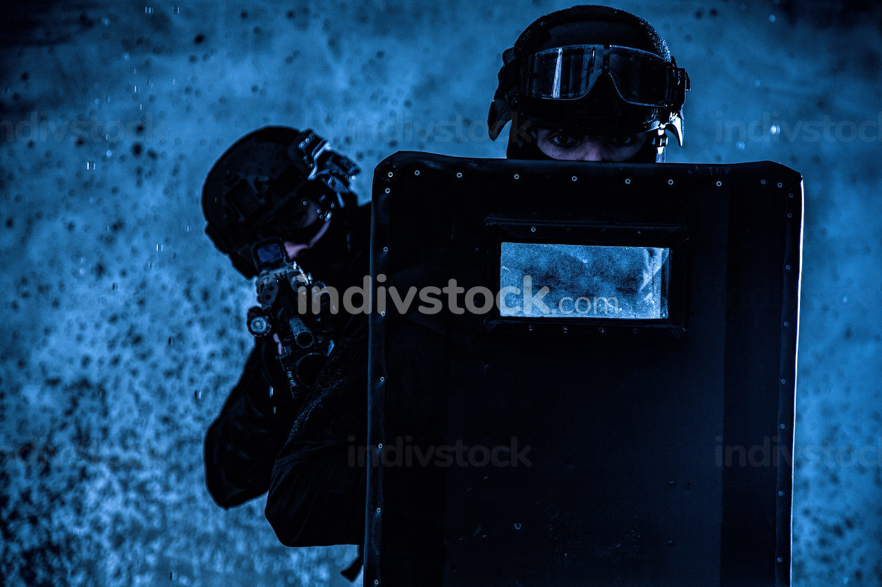 Counter terrorist squad members, police quick reaction, tactical group shooters, two SWAT officers hiding behind, covering themselves with ballistic shield, aiming service rifle, moving through fire