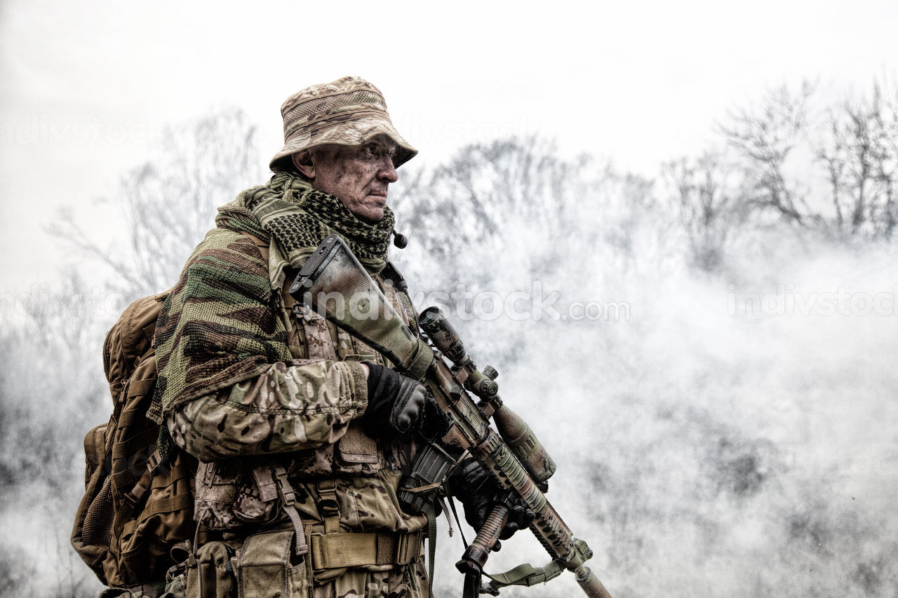 Elite commando fighter, private military company mercenary, army special forces veteran in camouflage uniform, shemagh and bonnie, equipped radio headset standing with sniper rifle in clouds of smoke