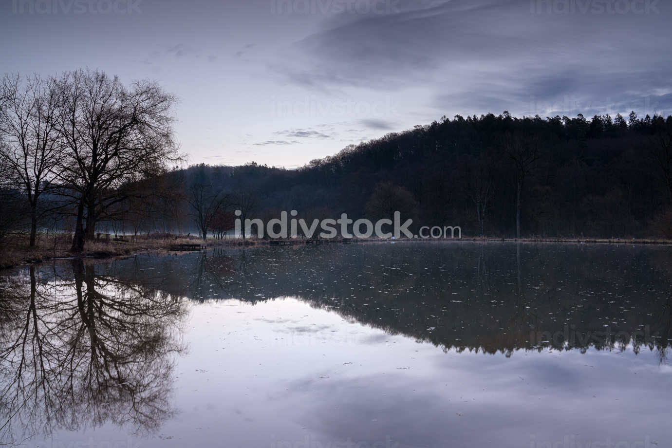 Fishpond close to Lindlar with water reflection during early morning mood, Bergisches Land, Germany