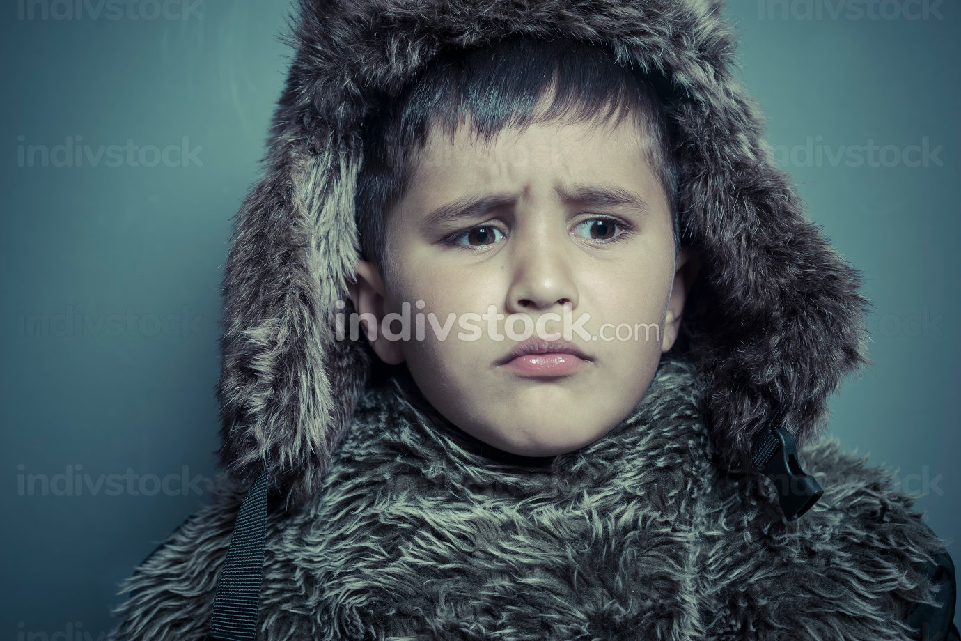 Funny child with fur hat and winter coat, cold concept and storm