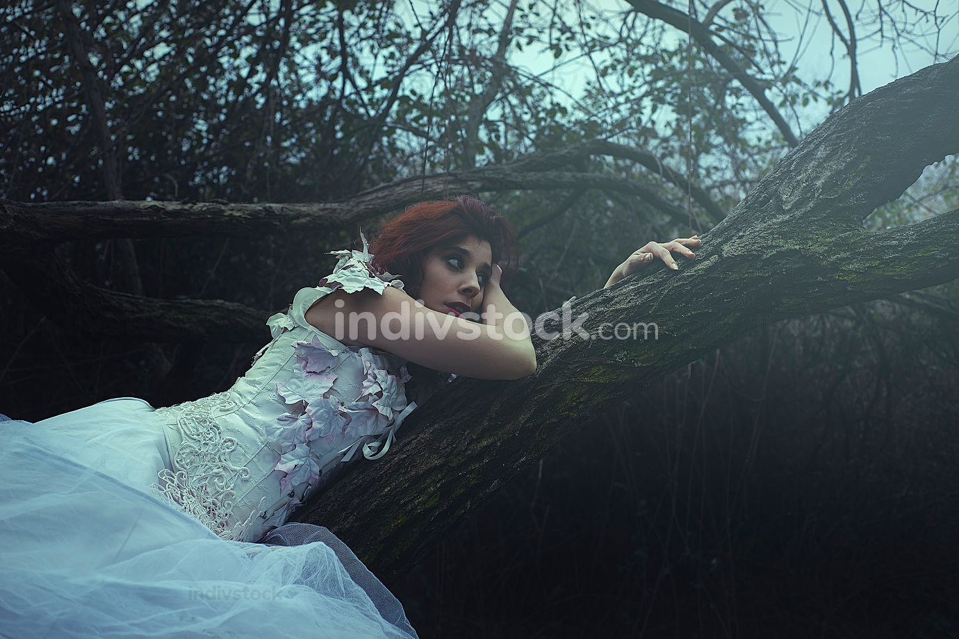 haired girl with white dress of leaves in a forest with colored