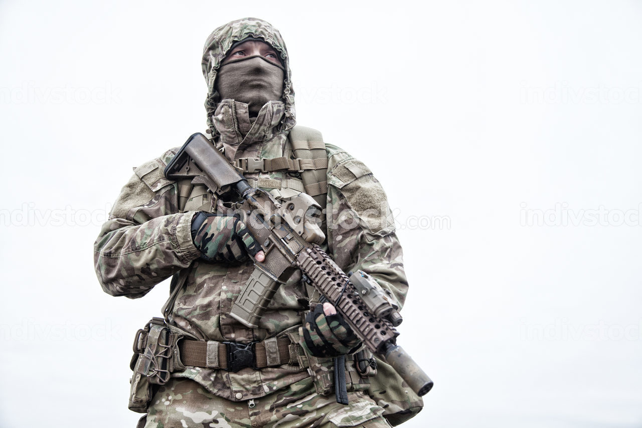 Irregular military mercenary, commando saboteur in camo jacket, wearing hood on head, armed service rifle, carrying tactical backpack during march, looking on distance