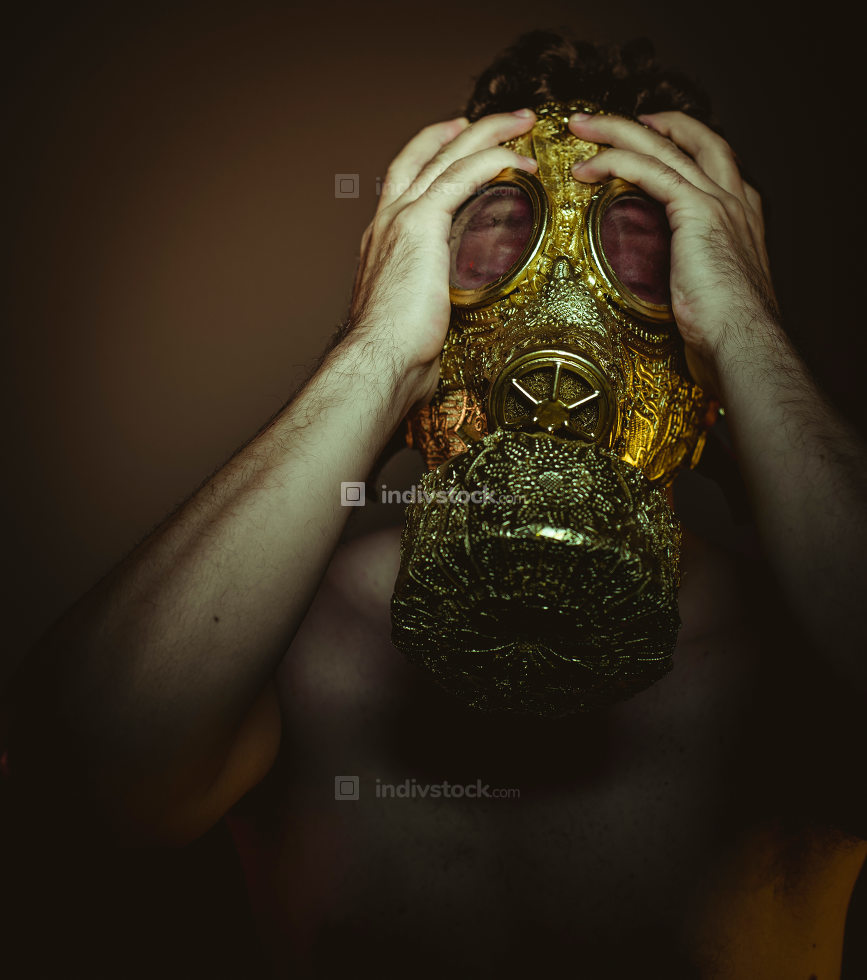 Man with gold gas mask and arabesques in poses of drowning and d