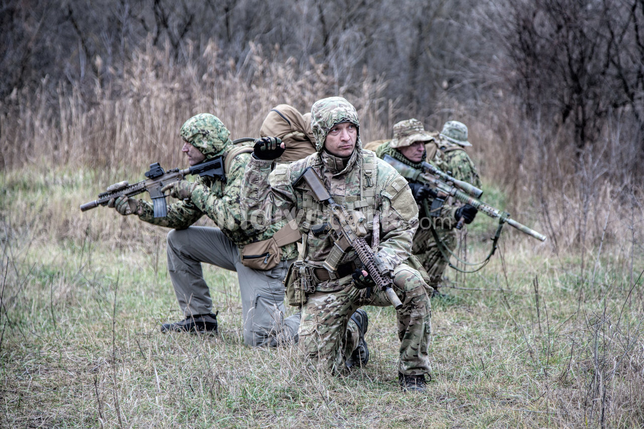 Military army soldiers tactical team, commando group moving cautiously in forest area, kneeling and looking around, covering comrades, controlling sectors. Commander showing halt or stop hand signal