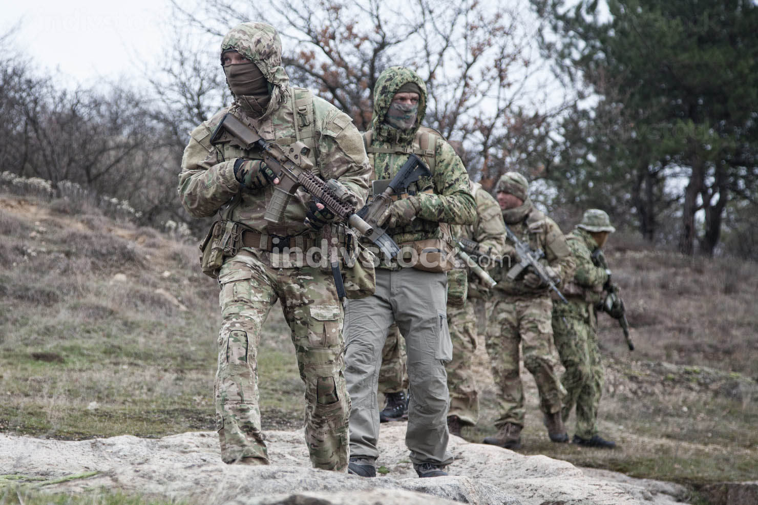 Military team, private military company mercenaries group in camouflage military uniform and mask, armed service rifles, walking in line behind commander, patrolling area in forest
