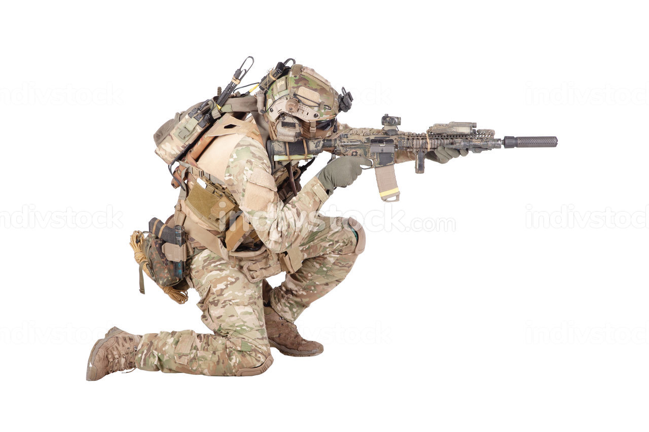 Modern army infantry soldier in combat uniform and helmet standing on knee, aiming with laser sight on service rifle, shooting in enemy during firefight studio shoot isolated on white background