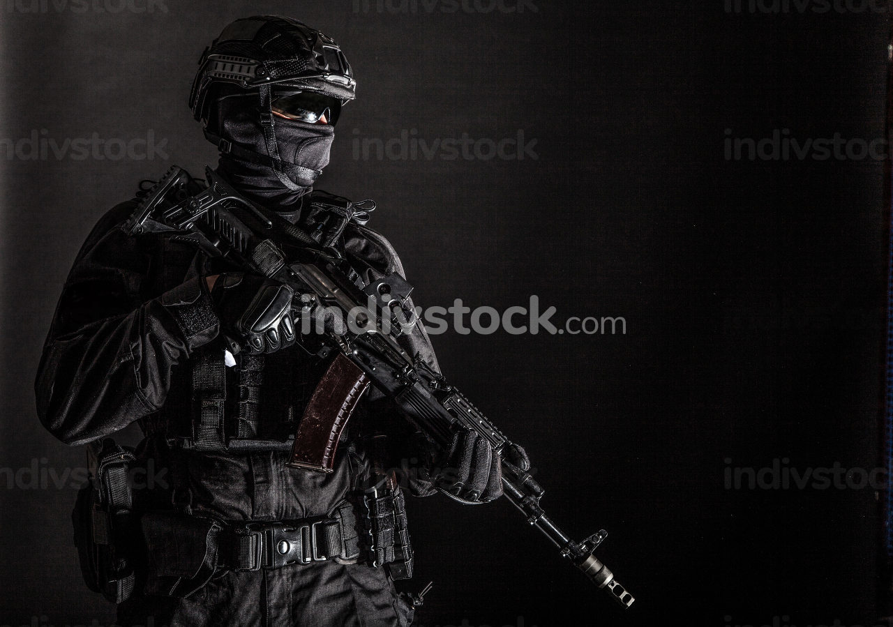 Police special forces, quick reaction team officer, tactical group fighter in black uniforms, helmet and hidden behind mask identity, armed with assault rifle, low key studio shoot on black background