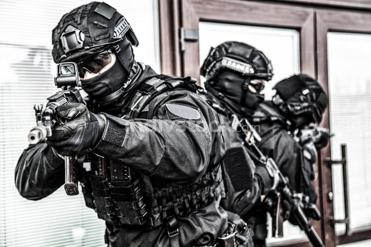 Police special operations immediate reaction team members in blank black uniform, tactical ammunition and mask, armed with assault rifle covering each other during hostage rescue or security operation