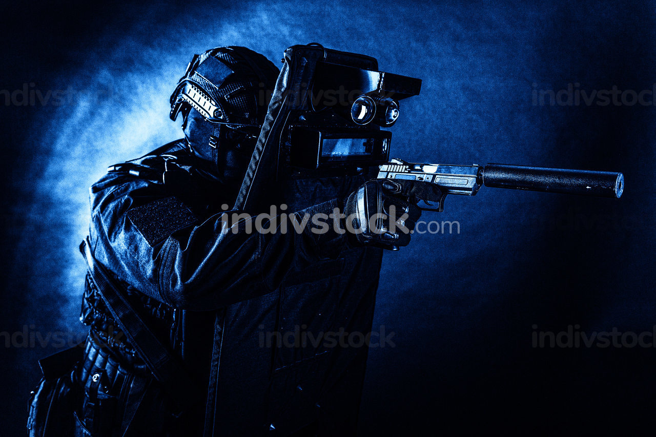Police special operations team, quick response group fighter in black uniform, helmet and mask aiming with pistol equipped silencer while hiding behind ballistic shield, toned, low key studio shoot