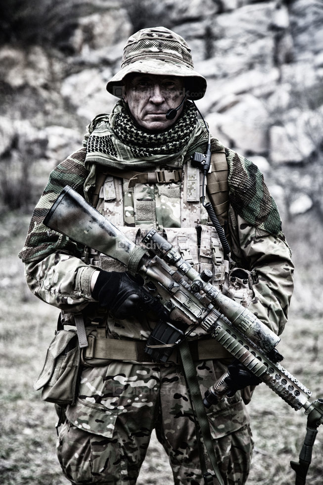 Portrait or commando veteran, experienced and skilled mercenary, army special forces sniper, counter-terrorism squad marksman in camouflage combat uniform, standing with sniper rifle in rocky area