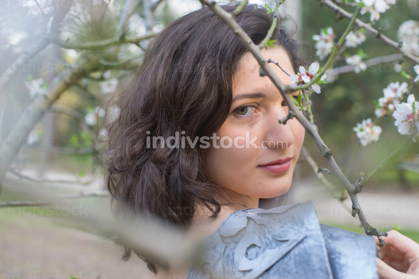 Season beautiful brunette girl dressed in armor in a grove of ch