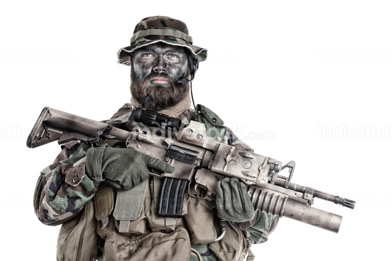 Serious commando fighter, military company mercenary with camouflage paint on bearded face, holding assault rifle with grenade launcher and laser sight, studio shoot isolated on white background