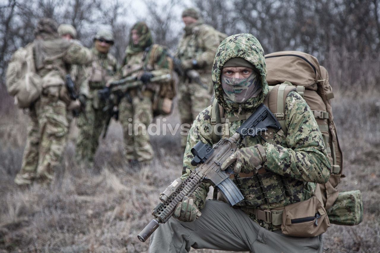 Shoulder portrait of army infantry soldier, tactical group member in camouflage uniform, carrying backpack, wearing camo jacket hood, hiding face with mask, looking in camera, comrades on background