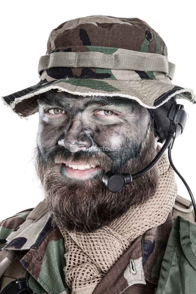 Shoulder studio portrait of commando soldier, modern mercenary, professional soldier with black camouflage paint on bearded face, tactical radio headset with microphone, isolated on white background