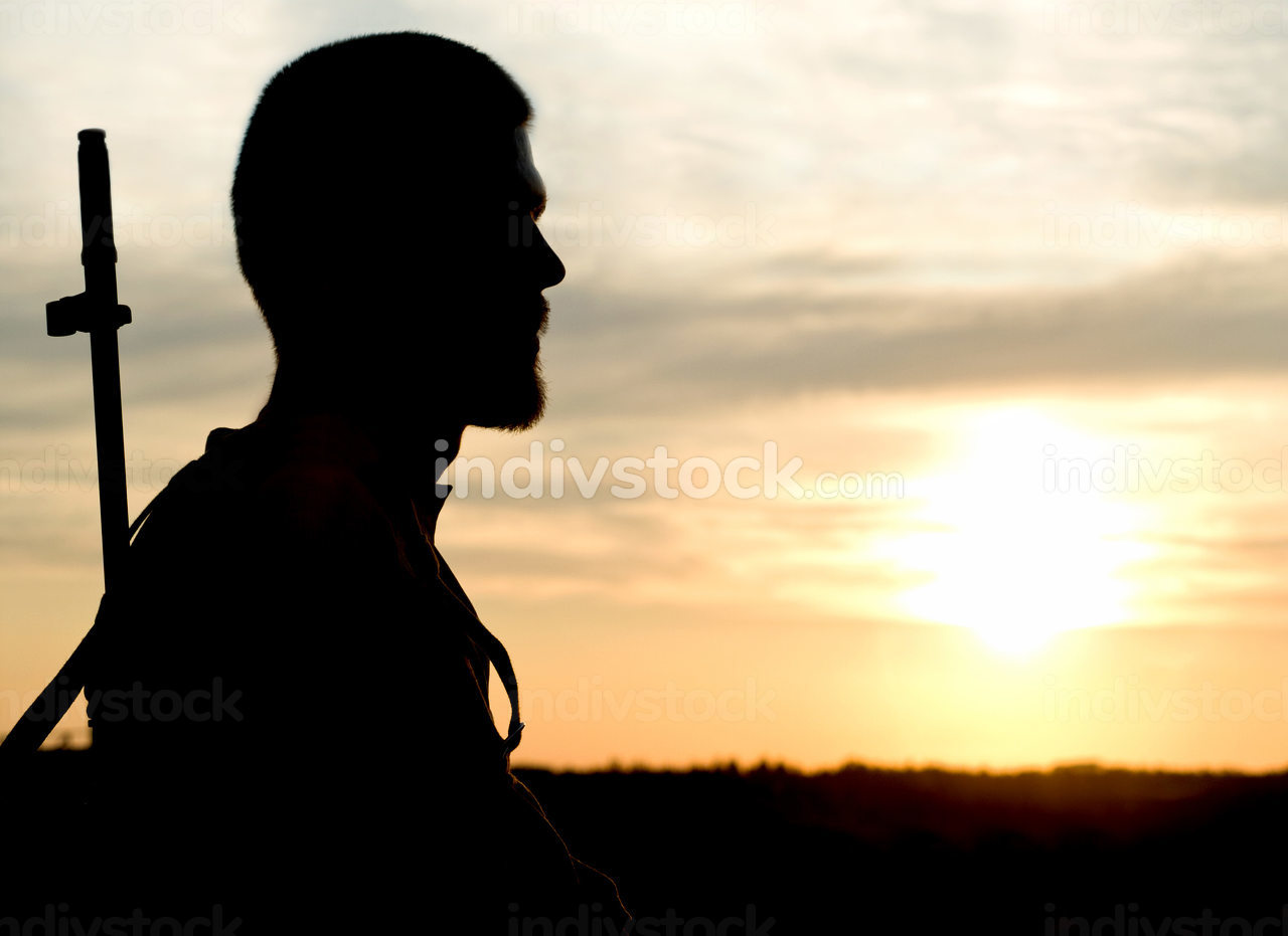 Silhouette of soldier with rifle against a sunset