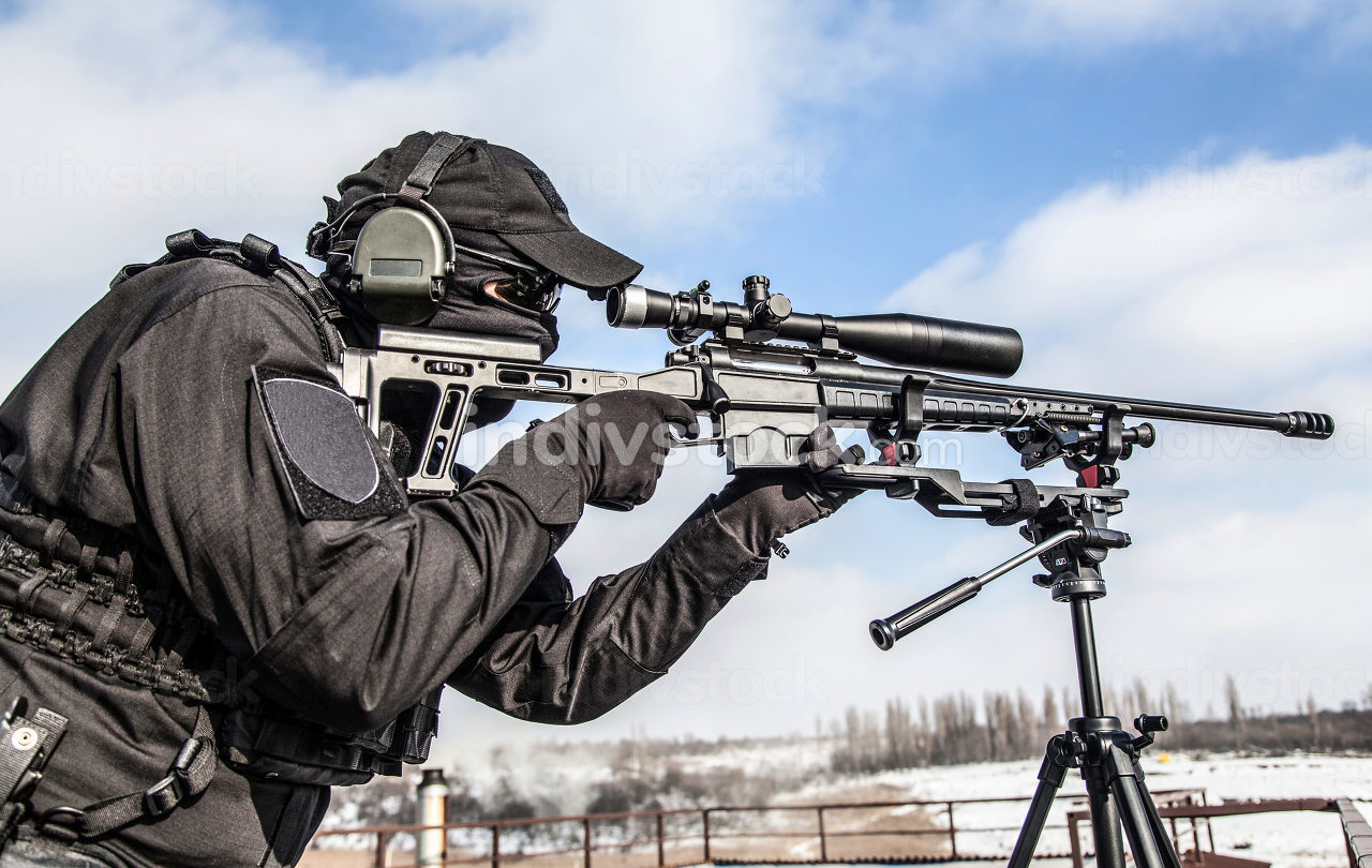 Sniper of police special operations tactical group in black uniforms, ballistic glasses and headphones, aiming with telescopic optical sight on sniper rifle mounted on tripod, over shoulder back view